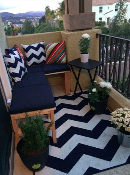Un semplice set di tavolino da caffè e due sedie dall'aspetto rustico è tutto ciò che serve per arredare uno spazio esterno. Per sfruttare al meglio uno spazio minuscolo, un tappeto rustico gettato proprio davanti al tavolo e alle sedie può aiutare a far sembrare il balcone più grande.