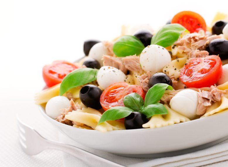 Condite la pasta con un filo d'olio, mozzarelline, pomodori e olive.
