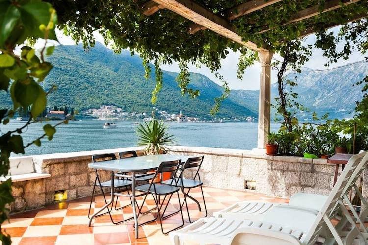Gli ospiti amano rilassarsi al sole su questa terrazza privata sul lungomare. La vista ininterrotta di due splendide isole della Baia di Kotor atterra questo appartamento sulla lista dei più famosi Airbank in Europa di Condé Nast Traveller.