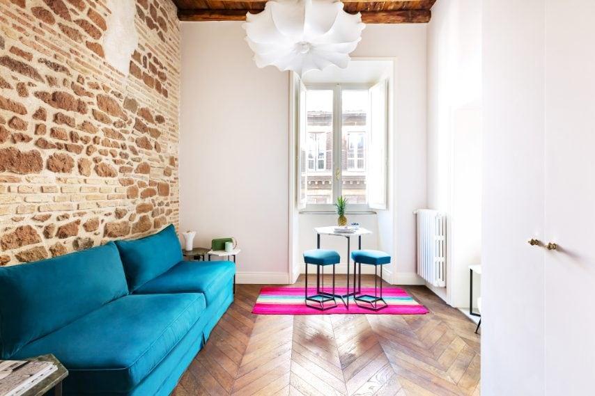 Geometrie, colori e dettagli creativi sono in ogni angolo di questo appartamento romano reso ancora più vivace dalla parete in mattoni a vista e dal parquet vintage.
