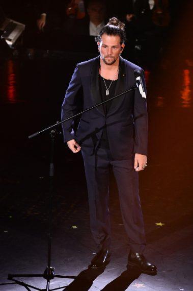 Smoking dai maxi rever tondi per il cantante che sdrammatizza l'abito formale con shirt dallo scollo tondo e anelli vistosi. VOTO 7