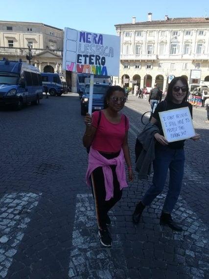 Due ragazze sorridono e mostrano i loro cartelli di fronte alla fila delle auto della Polizia