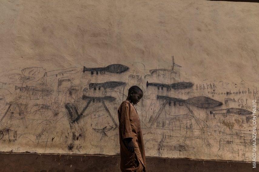 Un ragazzo orfano davanti un muro con disegni raffiguranti lanciagranate a razzo, a Bol, Ciad.