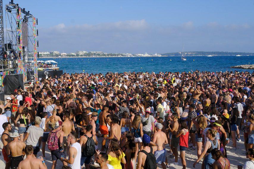 """Dimenticate il défilé delle star, la folla di fan, le corse dei paparazzi e le cene di gala, ad agosto la Croisette, nel cuore della città di Cannes, diventa la location per una delle più grandi """"feste in spiaggia"""" europee che attira frequentatori di festival da tutto il mondo."""