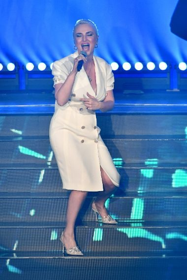 La cantante sul palco al fianco di Marco Masini con un abito bianco e capelli cortissimi biondo platino