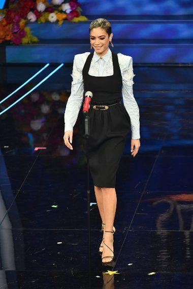 La cantante sceglie un trendy look con abito nero su camicia dalle spalline pronunciate