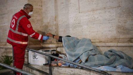 Coronavirus, gli addetti della crocerossa aiutano i senza tetto a Roma