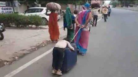 La madre trascina il trolley e il figlio esausto che dorme sopra: il dramma Covid19 in India
