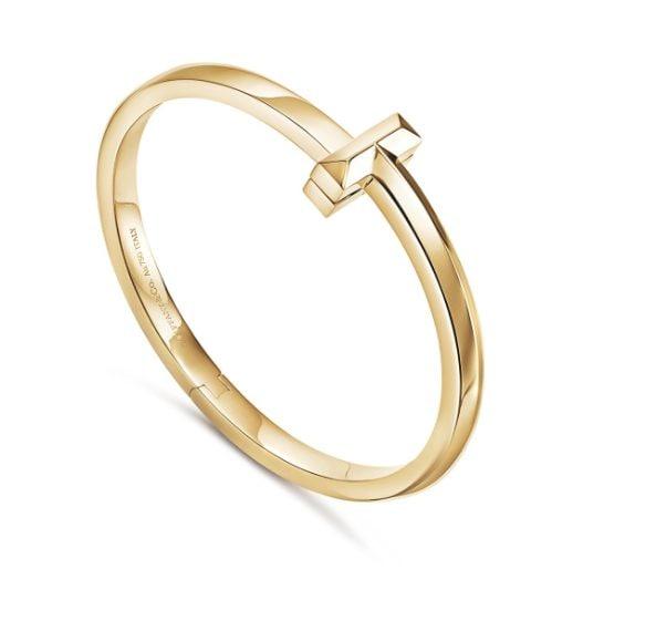 """Bracciale in oro giallo a cerchio, con incisione interna e chiusura superiore che richiama l'iconico motivo a """"T""""."""