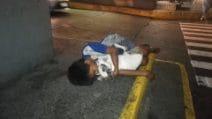 Il bimbo senzatetto che dorme abbracciato al suo cane sul marciapiede