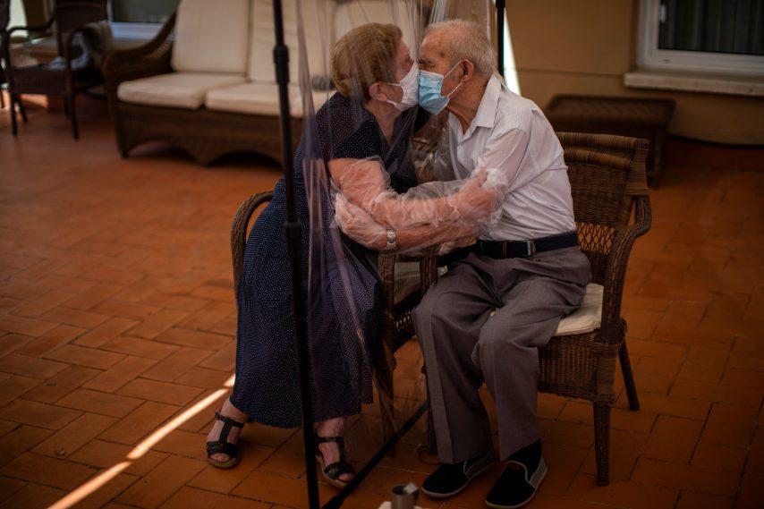 Agustina Canamero, 81 anni, e Pascual Perez, 84 anni, si abbracciano e si baciano attraverso uno schermo di pellicola di plastica per evitare di contrarre il coronavirus in una casa di cura a Barcellona, in Spagna, il 22 giugno 2020 (AP Photo / Emilio Morenatti)