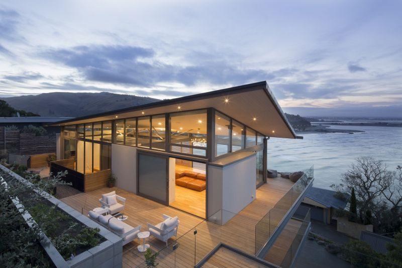 Situata su una sezione collinare estremamente difficile, questa casa su tre livelli è stata progettata per collegare la spiaggia di Christchurch con le colline boscose. Un'impronta economica, pannelli solari, serbatoi dell'acqua piovana, feritoie aeree automatiche, un bruciatore a legna a bassissime emissioni, finestre di alto livello, schermi scorrevoli, materiali a bassa manutenzione parzialmente ricavati dal materiale roccioso scavato locale e il tetto a vela deformato, progettato per seguire