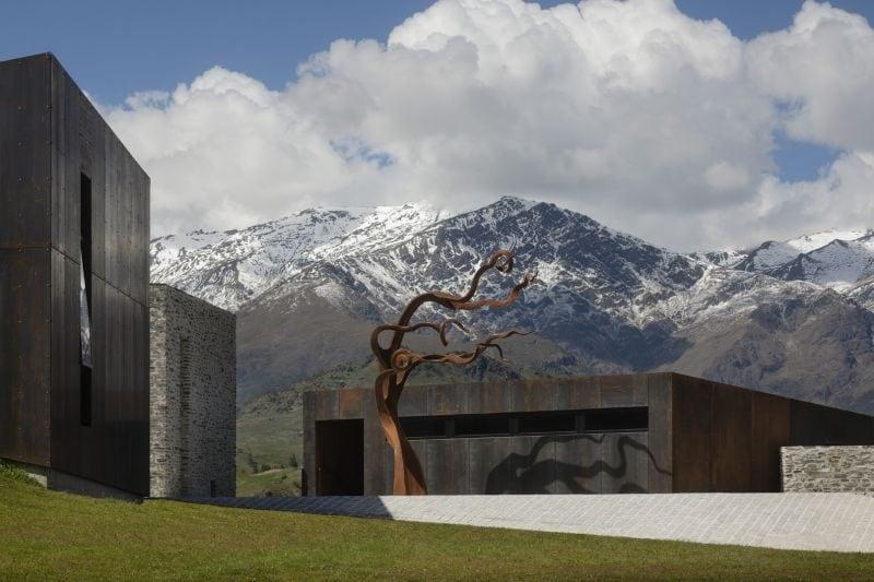 """Situata in un bacino alpino nelle Alpi della Nuova Zelanda, la Arrowtown House sorge dal paesaggio. La casa è concepita come una serie di padiglioni che, come le forme di roccia o resti di miniere d'oro arrugginite, contesto della zona. Incastonati nel terreno, seguono i contorni del terreno piuttosto che modificarli. La casa è """"della terra"""" piuttosto che """"della terra"""". Gli spazi sono orientati verso la vista sulle montagne e sono organizzati attorno a un cortile d'ingresso. Si accede alla casa"""