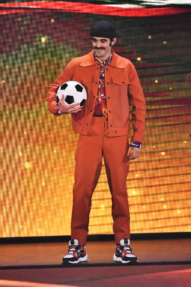 Il cantante indossa un originale completo arancione con una camicia a fantasia