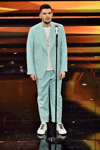 Il giovane cantante delle nuove proposte indossa per la serata un completo color pastello su shirt bianca