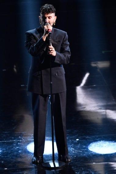 Elegantissimo e trendy il cantante sceglie un completo scuro con giacca doppiopetto con cuciture in vista