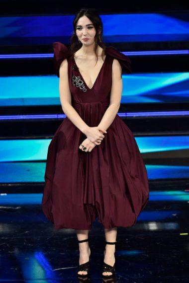 Per il palco l'attrice sceglie un abito borgogna dalla profonda scollatura con decoro gioiello