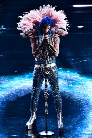 "Il performer indossa una tuta di paillettes argentate con piume rosa a ""armatura"" da rugby"