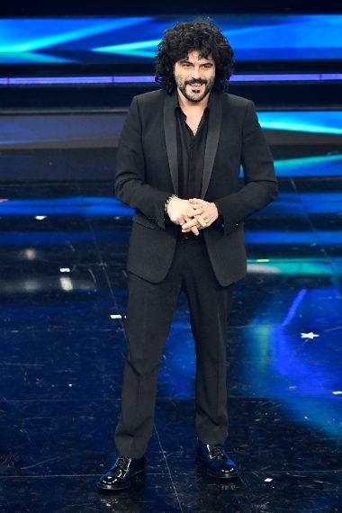 Il cantante indossa un tuxedo con rever a scialle in raso di seta nero, camicia di seta e stringate in pelle