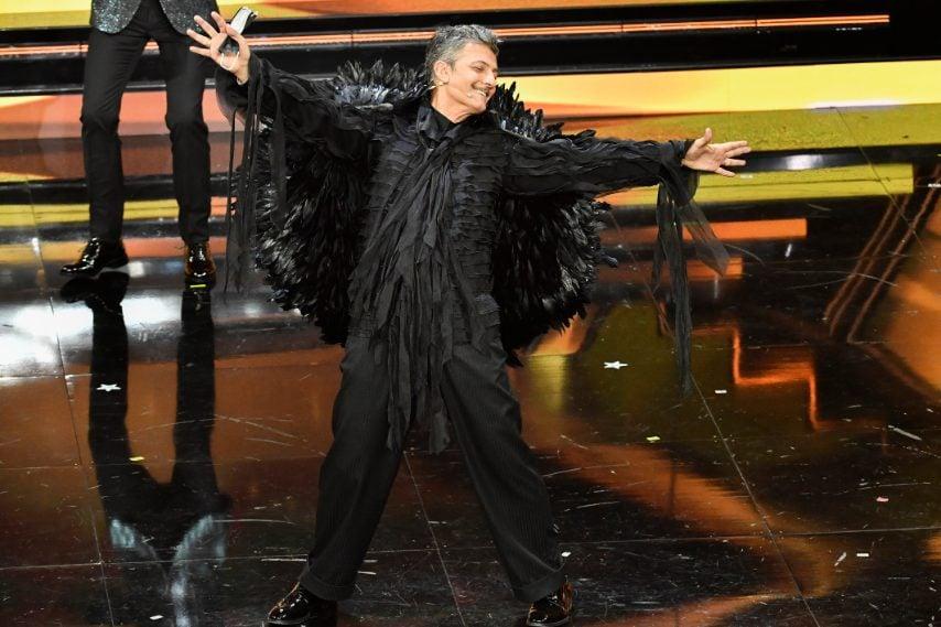 Il conduttore appare sul palco con sulle spalle una particolare impalcatura ricoperta di piume nere, imitando Achille Lauro