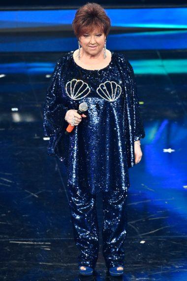 La cantante appare sul palco con una casacca oversize su pantaloni ricoperti di paillettes con conchiglie cucite sul seno
