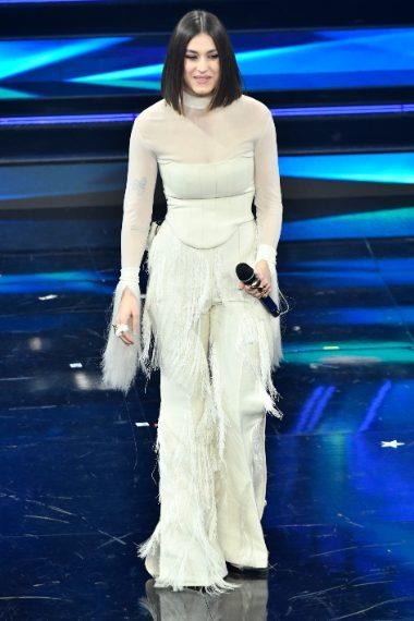 Total white per la cantante che indossa un corsetto e pantaloni a zampa di seta con lunghe frange