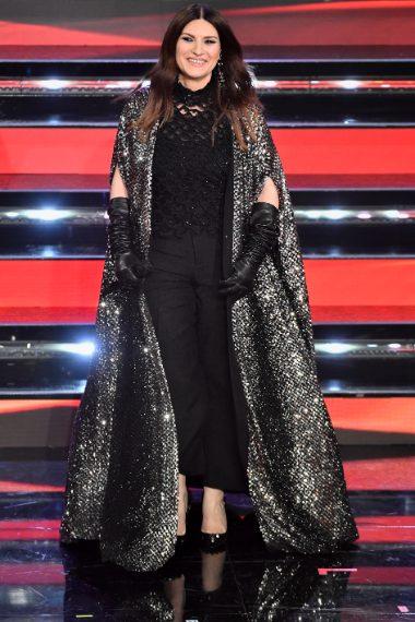 Lungo mantello luccicante su top traforato e pantaloni scuri per la cantante sul palco dell'Ariston