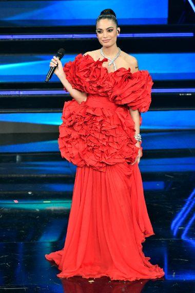 La cantante per la quarta uscita sul palco sceglie un abito ancora rosso asimmetrico con vaporose ruche