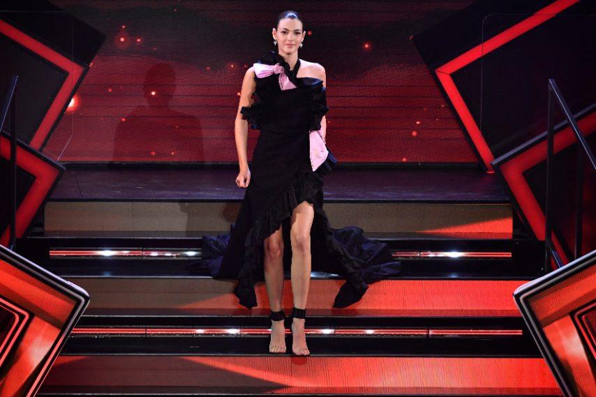 La top model per la prima apparizione sul palco sceglie un lungo abito nero con ruches e maxi spacco con dettagli rosa confetto