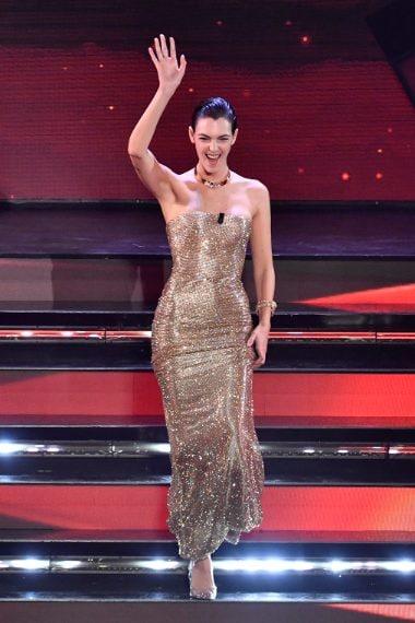 Per la seconda uscita sul palco la modella sceglie un tubino strapless coperto di cristalli
