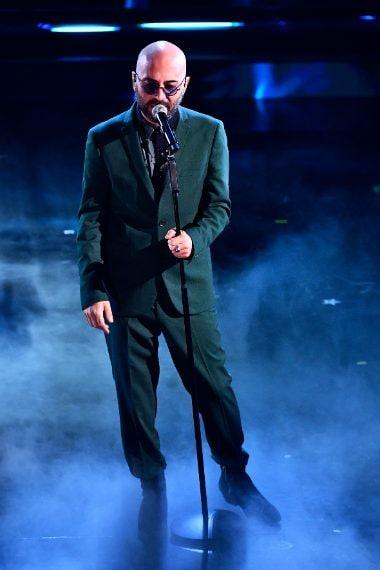 Il cantante sceglie per il palco un completo verde bottiglia e camicia a stampa