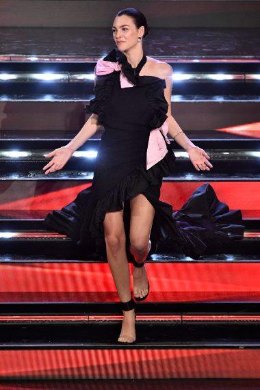 La modella sceglie un lungo abito scollato lateralmente con ruches e dettagli rosa sotto il total black