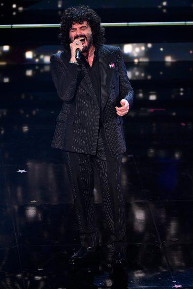 Abito doppio petto gessato con bordino e bottoni ricoperti in faille, camicia in popeline nero e stivaletti neri per il cantante
