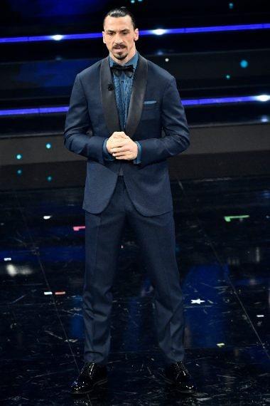 Il calciatore indossa uno smoking blu con rever neri a contrasto