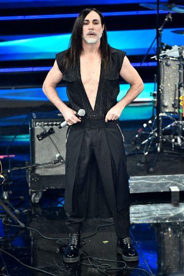 Il cantante sceglie un completo scuro con camicia smanicata