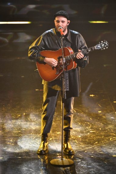 Camicia in pelle su pantaloni scuri per il cantante