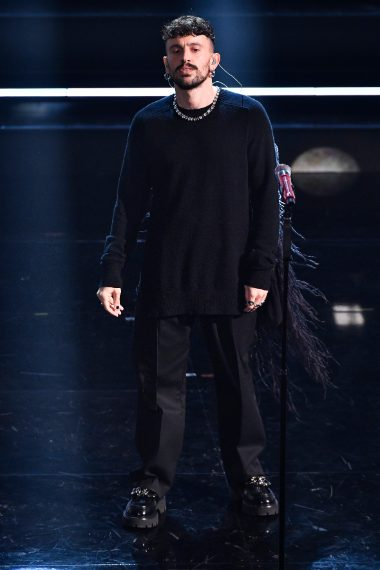 Il cantante indossa una particolare shirt con applicazione di piume sulla schiena