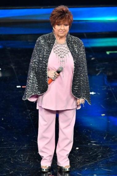 La cantante sceglie un look rosa pastello con mantella luccicante