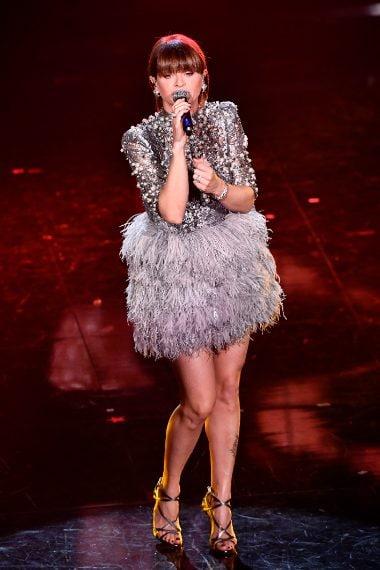 Pizzo e perle caratterizzano questo look della cantante con gonna di piume