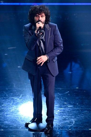 Uno smoking blu dai rever a lancia caratterizza il look del cantante