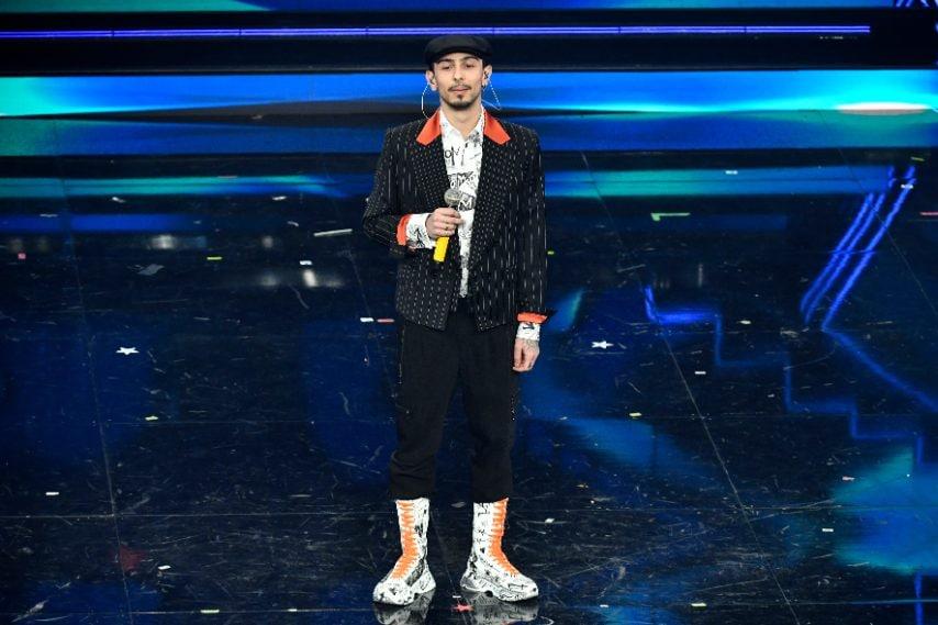 Giacca gessata su camicia e sneakers graffiti per il cantante sul palco