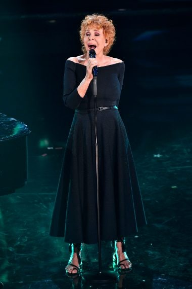La Vanoni indossa un abito nero con scollo a barca