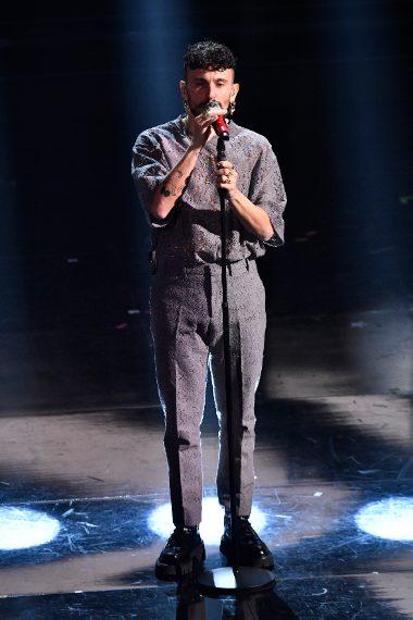 Il cantante indossa una shirt in pizzo e pantaloni vita alta