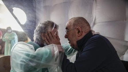L'abbraccio tra il marito ricoverato e la moglie: separati dalla protezione in plastica