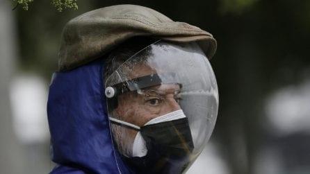Doppia maschera e un'ampolla in testa: così si protegge dal covid un uomo in strada