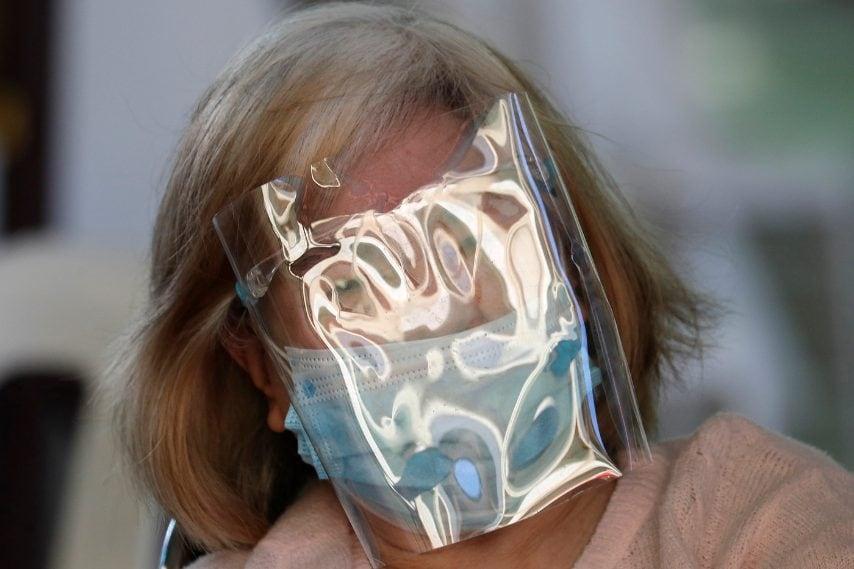 Una donna anziana che indossa uno schermo facciale attende dopo essere stata inoculata con il vaccino cinese Sinovac COVID-19 nella città di Quezon, nelle Filippine
