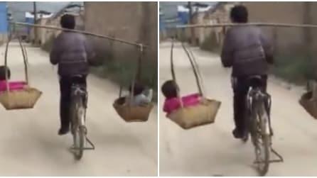 Non c'è posto sulla bici, ecco il padre come porta in giro i figli
