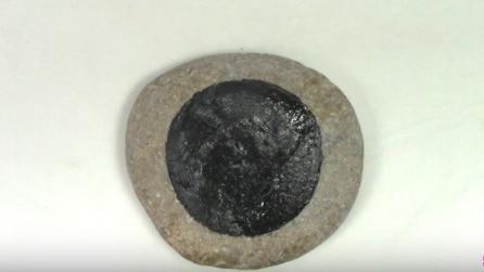 Disegna un cerchio nero sulla pietra, quello che realizza è unico