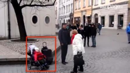 L'artista di strada si esibisce, ma tutti sono attratti da sua figlia nel passeggino: la scena è da brividi