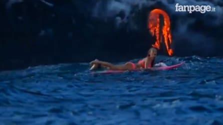 Fa surf in bikini durante l'eruzione di un vulcano: le immagini che lasciano senza parole